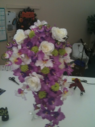 Cascading purple, green, and white orchid bouquet